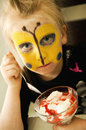Girl with buterfly painted face a cute pretty a butterfly image on her eating a tasty dessert Royalty Free Stock Image