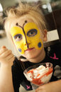 Girl with buterfly painted face a cute pretty a butterfly image on her eating a tasty dessert Stock Photos