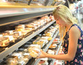 Girl buying cakes in supermarket side view of young blond fresh Royalty Free Stock Photos