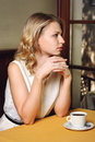 Girl in cafe with cup of coffee blond woman sitting a and looking out the window drinks the restaurant Royalty Free Stock Photo