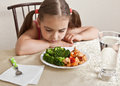 The girl calmly looks at the dish with meat and broccoli rested her head on table Stock Image