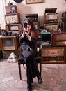 Girl with camera in antique shop young suit sat old Royalty Free Stock Photos