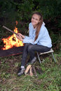 Girl at campfire a happy teenage sitting a Royalty Free Stock Photo