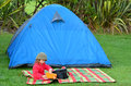 Girl on camping holiday young having a picnic outside a tent outdoor concept photo of child children outdoor nature Stock Images