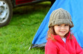Girl on camping holiday young smiling while looking away from the camera relaxing outside a tent outdoor concept photo of child Royalty Free Stock Photography