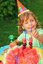 Girl in cap eats fruit in garden,happy birthday Royalty Free Stock Photos