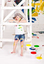 Girl in a cap with paints little smeared paint sits on scaffolding Royalty Free Stock Photos