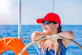 Girl captain on board of sailing yacht on summer cruise. Travel adventure, yachting with child on family vacation. Royalty Free Stock Photo