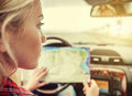 Girl in car with roads map Stock Images