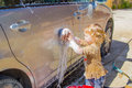 Girl car washing cute little is helping to carwash Royalty Free Stock Images