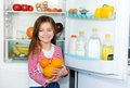 Girl carrots background refrigerator Royalty Free Stock Photography