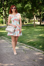Girl carrying bag young woman walking in a park and carry Stock Image