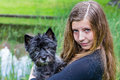 Girl carrying black dog on arm in nature blonde caucasian teenage front of water Royalty Free Stock Photo