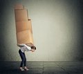 Girl carrying several boxes on her back in equilibrium holding Royalty Free Stock Photography