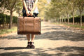A girl carrying a suitcase on a pathway travel concept Stock Photos