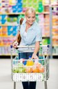 Girl with cart full of food in the shop concept consumerism retail and purchase Royalty Free Stock Images