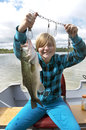 Girl Catching Big Bass In Boat On Lake Royalty Free Stock Photo