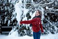 A girl of Caucasian appearance in a burgundy sweater throws snow. Outdoor games. Winter day, snowy park Royalty Free Stock Photo