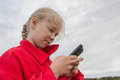 Girl with cell phone and cloudy sky Royalty Free Stock Photo