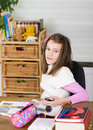 Girl with cell phone school and open book in her room Royalty Free Stock Photo