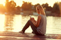Girl with cellphone sitting on dock Royalty Free Stock Photo
