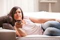 Girl changing programme on her television young woman watching tv sofa in living room using a gray remote control Stock Photo