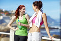 Girl chat out on the promenade two sporty outdoor women talking while exercising at beach Royalty Free Stock Photography