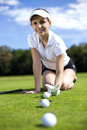 Girl cheating on golf field pretty tried to push the ball with her finger Stock Photo