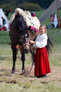 A girl cherish a horse moscow region september dressed in red skirt and whit blouse brown green trees foliage bacgkround borodino Royalty Free Stock Photo