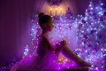 Girl child christmas tree lights kid in holiday night as angel with fairy star cute interior room pink purple light color Stock Photo