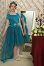 The girl child in the glamorous dress standing next to the mirror, admiring herself Royalty Free Stock Photo