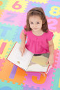 Girl child looking up from reading kids book Royalty Free Stock Images