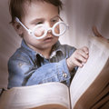 Girl child reading a magic book. Education, knowledge, wisdom, Royalty Free Stock Photo