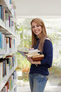 Girl choosing book in library and smiling Royalty Free Stock Images