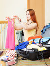 Girl choosing clothes for vacation sitting on sofa and Royalty Free Stock Images