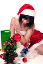 Girl in christmas hat beautiful wearing sitting on the floor and decorating new year tree Stock Image