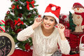 Girl in christmas hat beautiful wearing surrounded by holiday accessories and new year tree Royalty Free Stock Photo