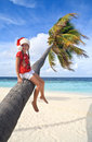 Girl in christmas hat sitting on a palm Stock Photos