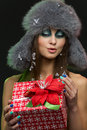 Girl with christmas present portrait of beautiful young in fluffy fur hat holding Stock Photography