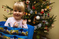 Girl beside christmas tree portrait of smiling blond little in gift bag decorated Stock Image