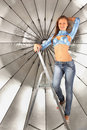 Girl climbed on ladder near silver umbrella Stock Images