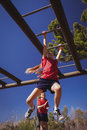 Girl climbing monkey bars during obstacle course training Royalty Free Stock Photo