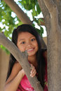 Girl climbing tree minority playing a Royalty Free Stock Photo