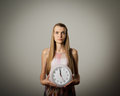 Girl and clock thinking holding in her hands time concept several minutes to twelve Stock Images