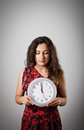 Girl and clock thinking holding in her hands time concept several minutes to twelve Stock Photography