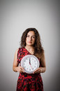 Girl and clock thinking holding in her hands time concept several minutes to twelve Royalty Free Stock Photos