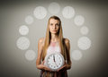 Girl and clock thinking holding in her hands time concept several minutes to twelve Stock Photos