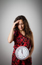 Girl and clock thinking holding in her hands time concept several minutes to twelve young woman doing something Royalty Free Stock Image