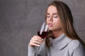 Girl with closed eyes drinking wine. Close up. Gray background Royalty Free Stock Photo