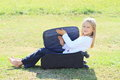 Girl in closing suitcase little blond black pants and white t shirt sitting black chech baggage Royalty Free Stock Images